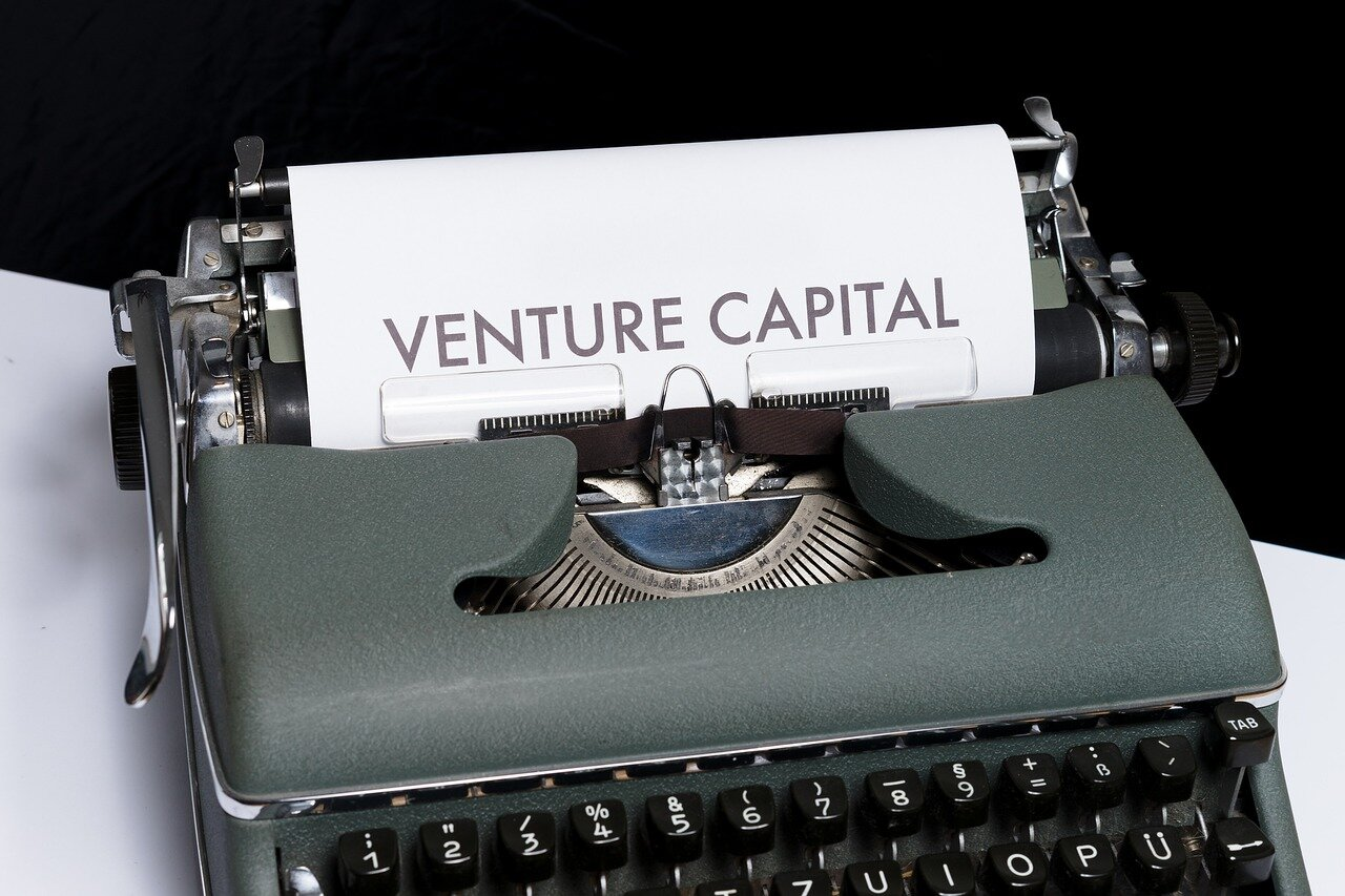"Image of a typewriter printing out the words ""venture capital""."